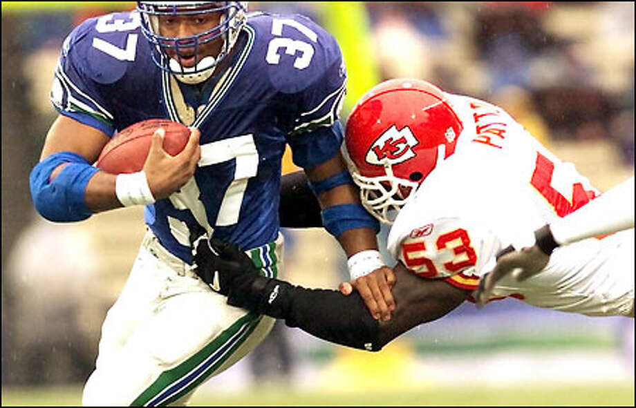 Shaun Alexander bursts past two Chiefs for a 15-yard gain in the third quarter. His 44-yard touchdown later in the drive gave the Seahawks a 21-10 lead. Photo: Mike Urban, Seattle Post-Intelligencer