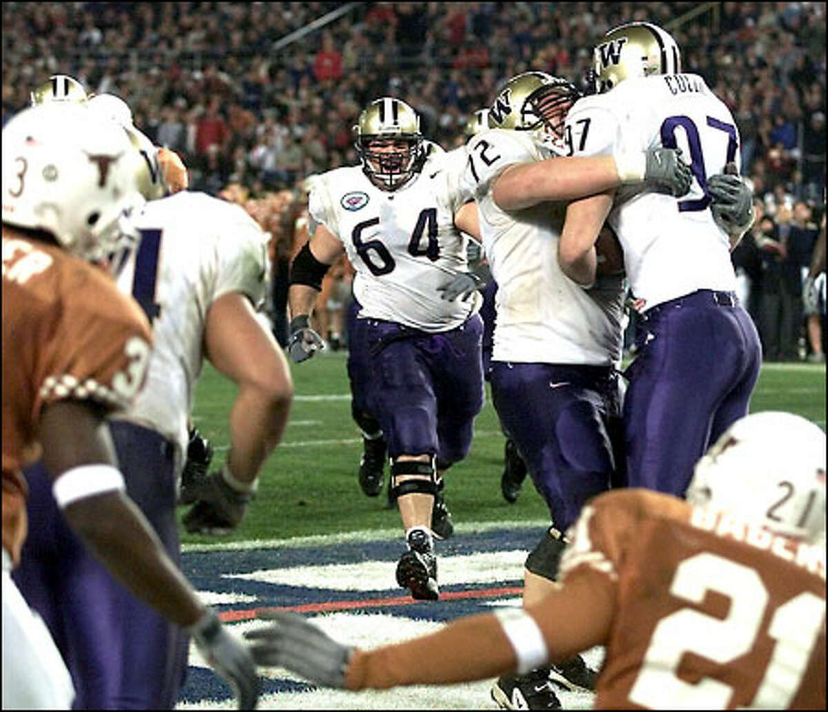 Senior tight end Joe Collier gets a bear hug from tackle Todd Bachert after scoring on a 4-yard pass from Cody Pickett to give the Huskies a 20-14 lead in the second quarter.