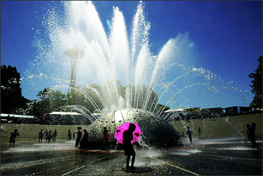 Isaiah Corpuz, 6, of Seattle says it's more fun playing in the Seattle Center International Fountain with an umbrella. Record-high temperatures scorched the Puget Sound region on July 21.