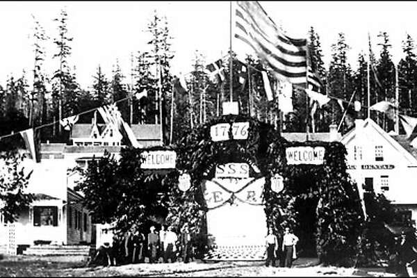 """An old-fashioned Fourth, 1865: Seattle pioneers gather at the corner of First Avenue and James Street next to celebrate the Fourth of July in 1865. The landmark Pioneer building and """"sinking ship garage"""" now straddle James Street at the site. Seattle's first July 4 celebration was observed in 1854 on the shores of Lake Union."""