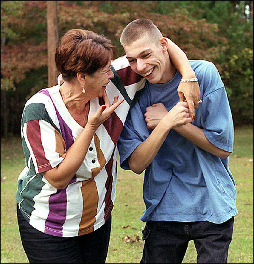 Jeb and his mom, Pat Locklear, talk about his day as he gets home from school. Pat took Jeb into her home as a preschooler, eventually adopting the boy, who was born deaf and who also has mild cerebral palsy and a developmental disability.