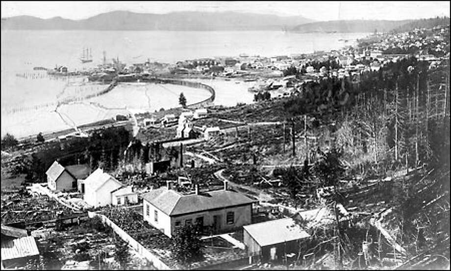 View of the harbor, 1880: The shape of Seattle's harbor was very different in 1880. This view from the vicinity of 12th Avenue South and South Dearborn Street shows the city's first rail line, the Columbia and Puget Sound Railroad, curving onto the jetty that held mills and wharves. Much of Elliott Bay inside the jetty was later filled. Photo: Vivian Carkeek Collection-Seattle Historic Society