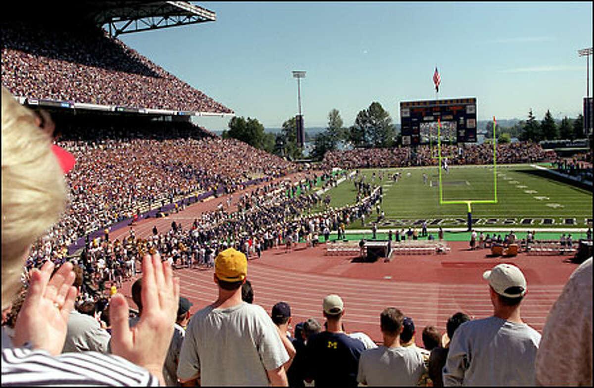Led by quarterback Cody Pickett, the UW football team files into Husky Stadium to begin its 2001 season.