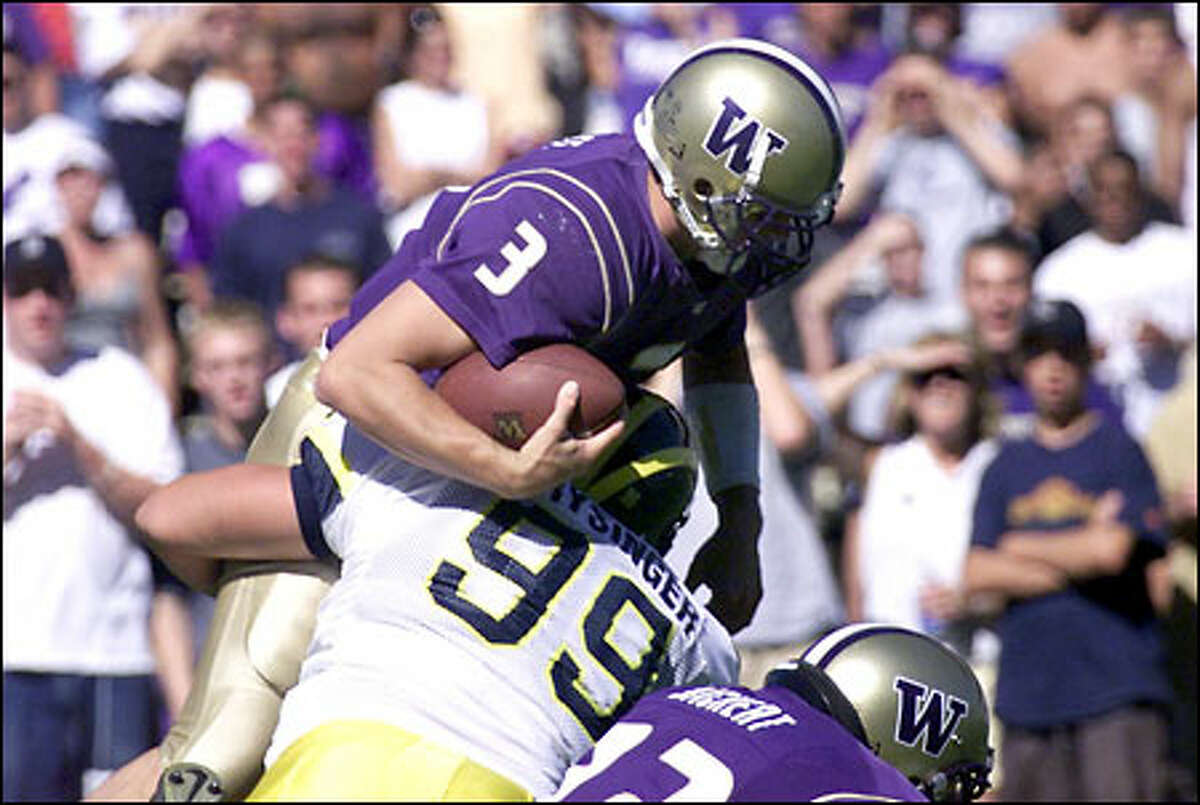UW quarterback Cody Pickett (3) is lifted off the ground as Michigan's Jake Frysinger (99) sacks him. In foreground is Todd Bachert (72).