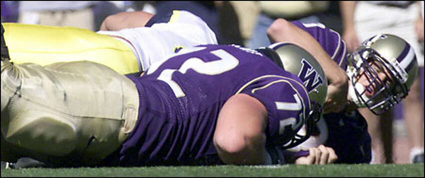 Husky quarterback Cody Pickett (3) grimaces as he hits the field after being sacked by Michigan's Jake Frysinger.