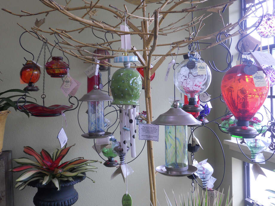 334 W. Sunset Road: Shades of Green displays bird feeders and wind chimes on a tree.