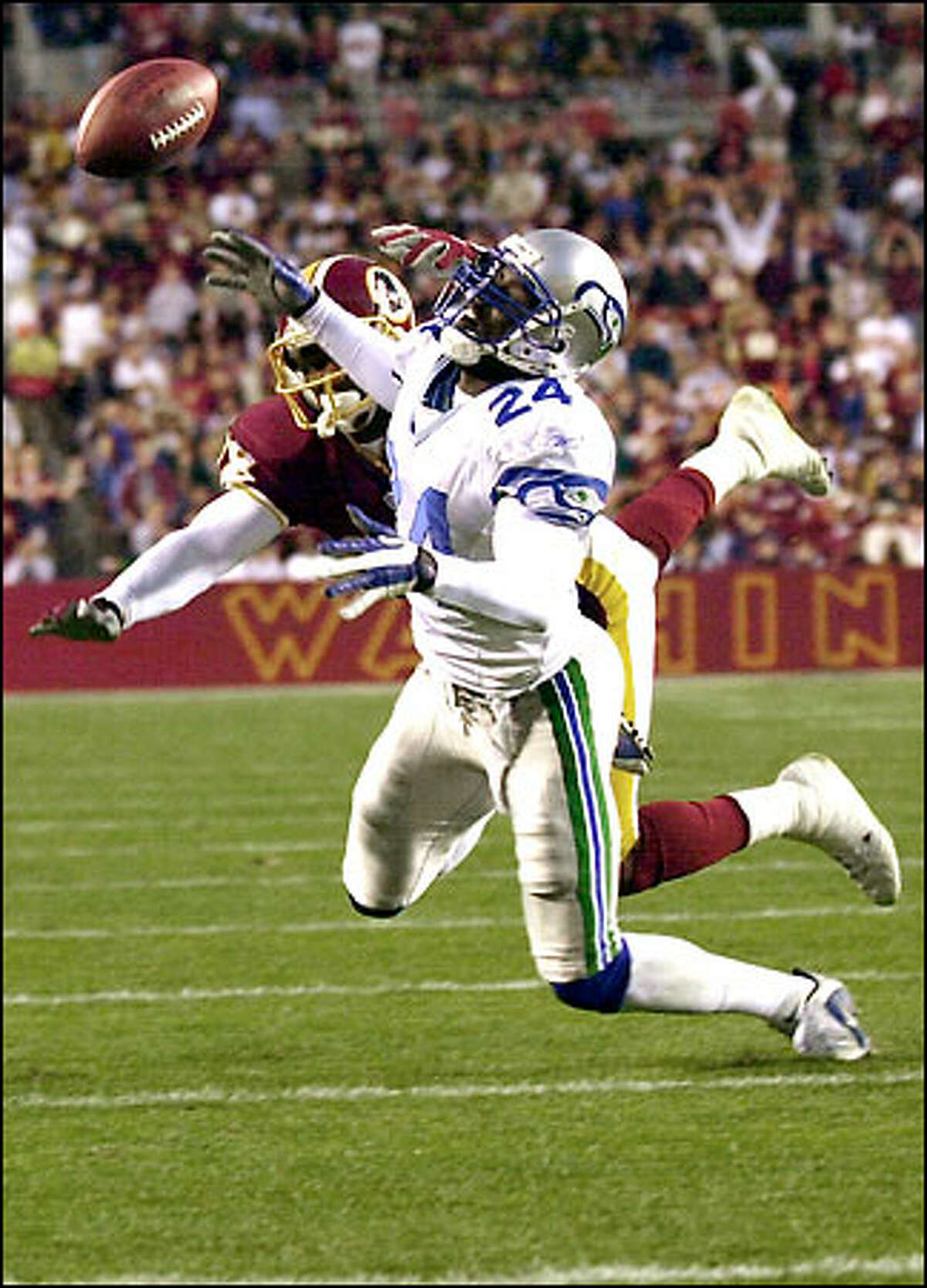 Seahawks cornerback Shawn Springs gets tangled up with Redskins wide receiver Derrius Thompson to break up a second-quarter pass.