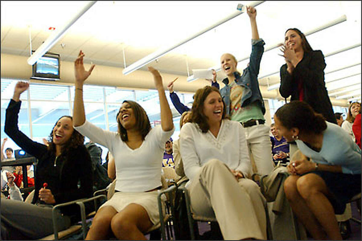 UW players -- from left, Angie Jones, Jill Bell, Andrea Lalum, Emily Autry and Cheryl Sorenson (seated), and Kayla Burt and Kristen O'Neill (standing) -- celebrate their NCAA Tournament bid.