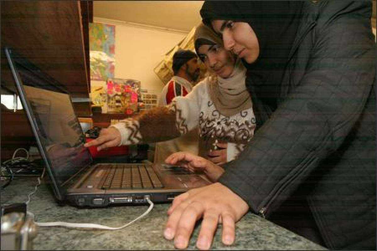Rabab Al Ali, 19, right, and her sister Haura Al Ali, 16 (pointing) checks out a Web site for information on the imminent execution of Saddam Hussein, at her father's Colby Halal Market in Everett. Their father, Lafta Al Ali, 41, waits on customer in background.