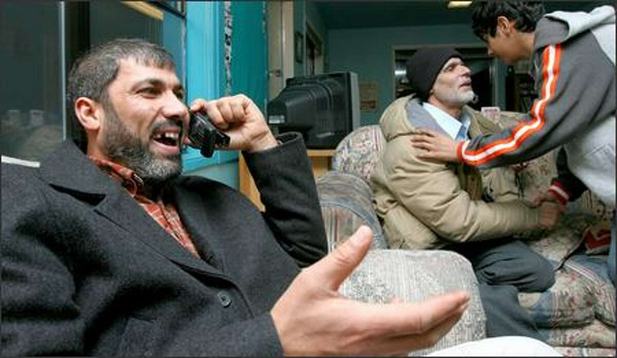 """Karim Al-Barkat, left, of Everett, talks with his brother in Samawa, Iraq, shortly after it was announced that Saddam Hussein was executed. Al-Barkat said his brother, 8,062 miles away, reported that people there were """"dancing in the streets."""" Members of the Everett Iraqi community meet in a North Everett Community center almost every evening."""
