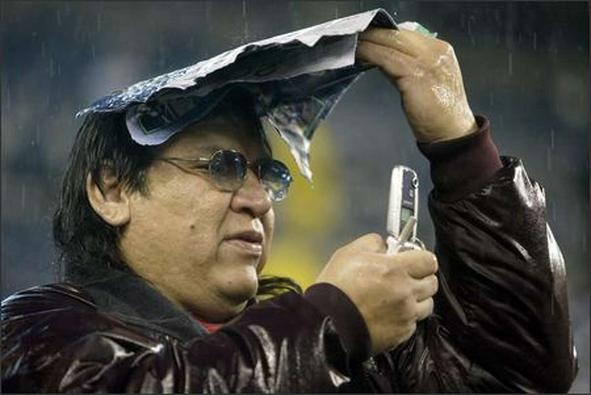 Kenneth Snell tries to make a cell phone call in the pouring rain at Qwest Field as he waits for the San Francisco 49ers game against the Seahawks at Qwest Field in Seattle on Thursday, Dec. 14.