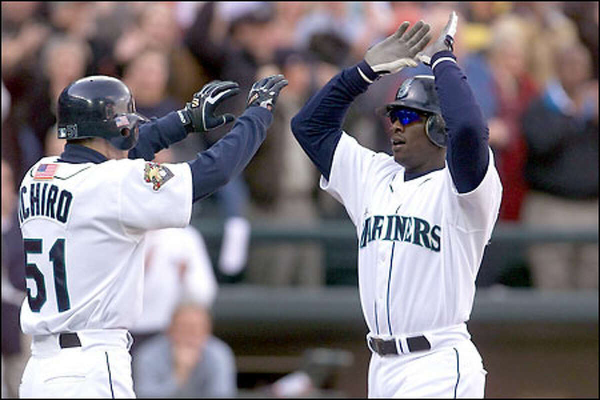 Ichiro Suzuki congratulates Mike Cameron for hitting a first-inning home run, on which Ichiro also scored, giving the Mariners a 2-0 lead to start the second game of the series.