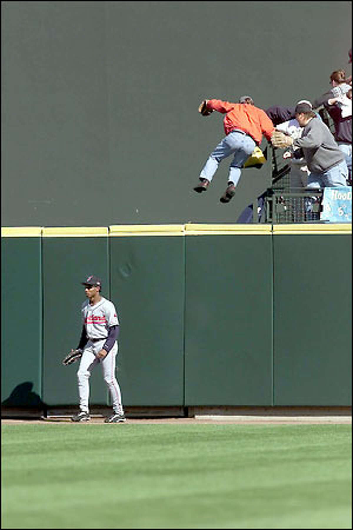 A Mariners fan jumps down from the stands to retrieve Edgar Martinez's first-inning home-run ball as Cleveland's Kenny Lofton stands by helplessly below.