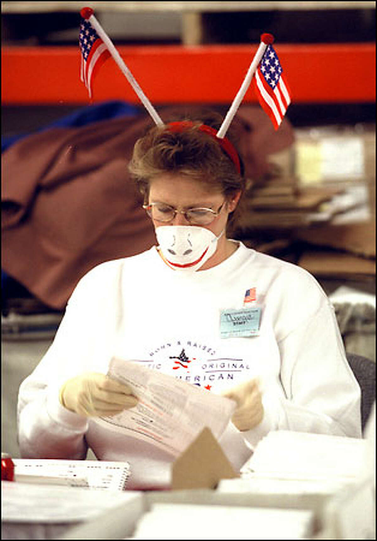 At the Mail Ballot Operation site in South Seattle, Georgia White makes the best out of having to wear a mask and surgical gloves because of anthrax concerns. White and her colleagues were the first to open and inspect mail in ballots for yesterday's election.