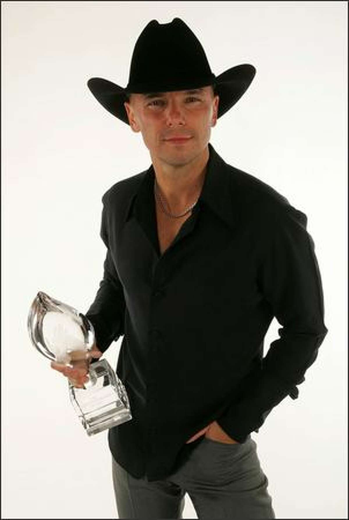 Musician Kenny Chesney poses in the portrait studio with his Favorie Male Singer Award during the 33rd Annual People's Choice Awards held at the Shrine Auditorium on January 9, 2007 in Los Angeles, California.