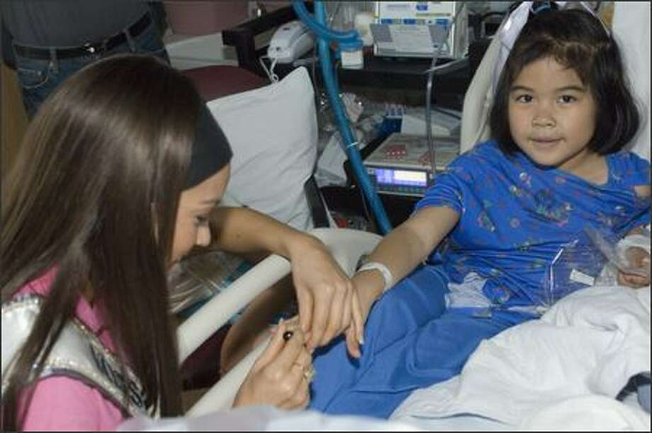 "Helen Salas, Miss Nevada USA 2007, helps make Aeris Deleon a ""Queen for a Day"" at Childrens Hospital Los Angeles on March 16. Photo: Miss Universe L.P., LLLP"