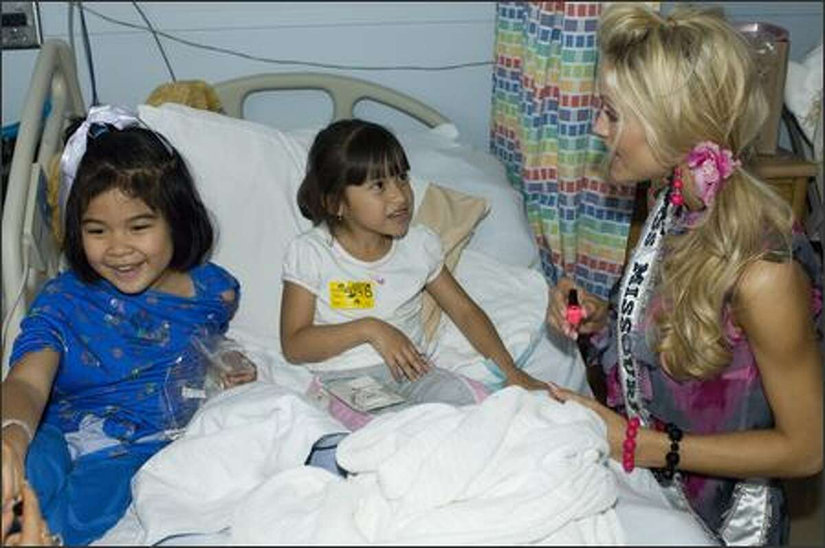 Amber Marie Seyer, Miss Missouri USA 2007, helps make Aeris Deleon and Leslie Roque
