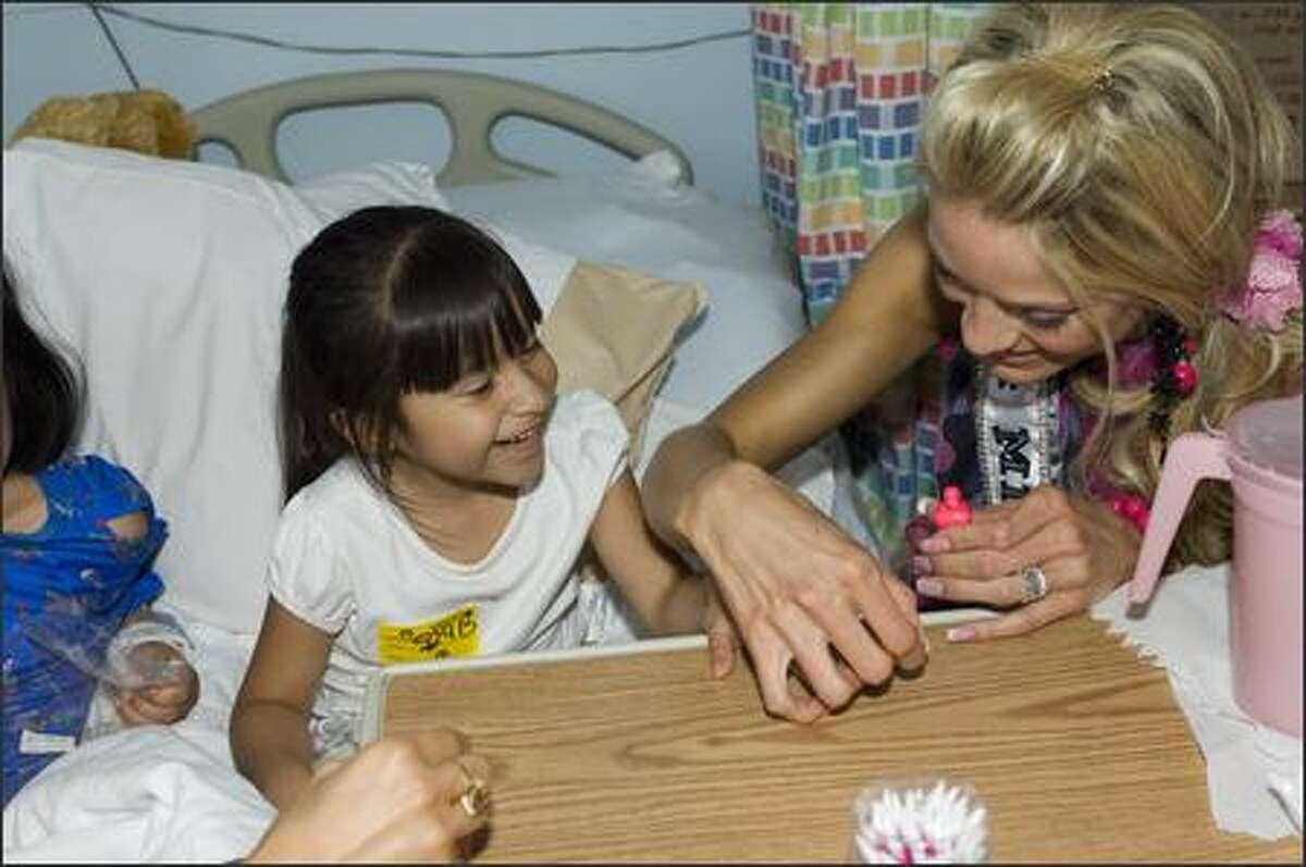 Amber Marie Seyer, Miss Missouri USA 2007, helps make Leslie Roque a