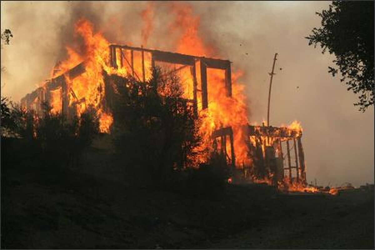 A wildfire burns a home located along Twin Pines Road near Cabazon,Calif., Thursday. (AP Photo/The Press Enterprise, William Wilson Lewis III)