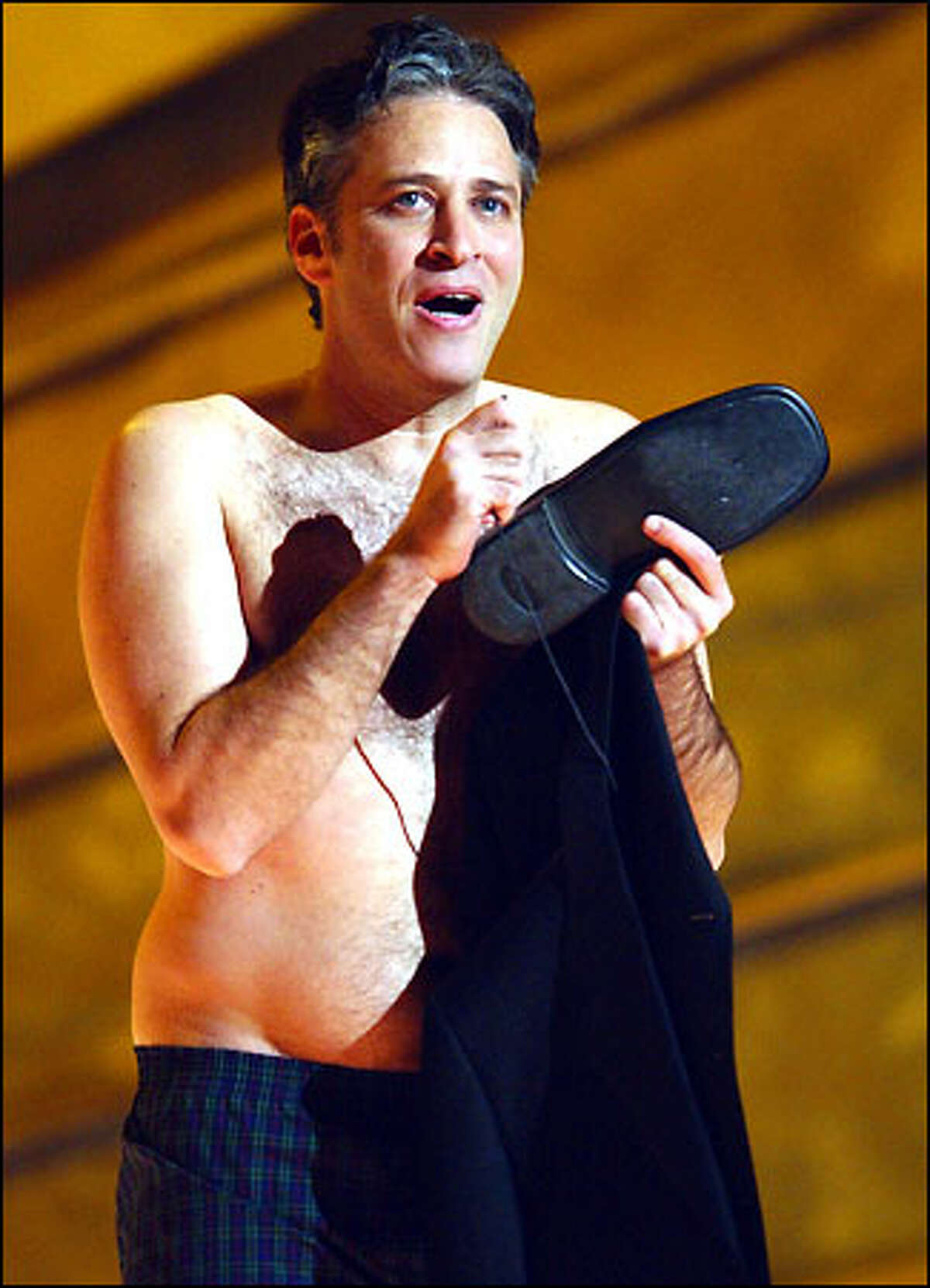 Jon Stewart holds onto his clothes after going through a mock security check as he arrives on stage to host the 44th annual Grammy Awards, Wednesday, Feb. 27, 2002, in Los Angeles.
