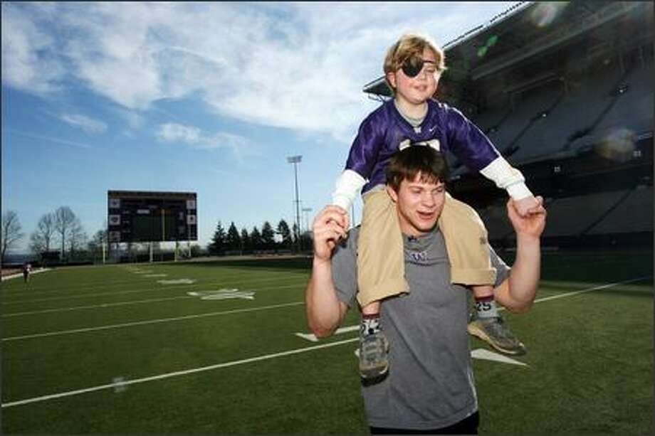 Quarterback Jake Locker carries Kyle, 6, during a spirited get-together Tuesday at Husky Stadium. Photo: Grant M. Haller, Seattle Post-Intelligencer