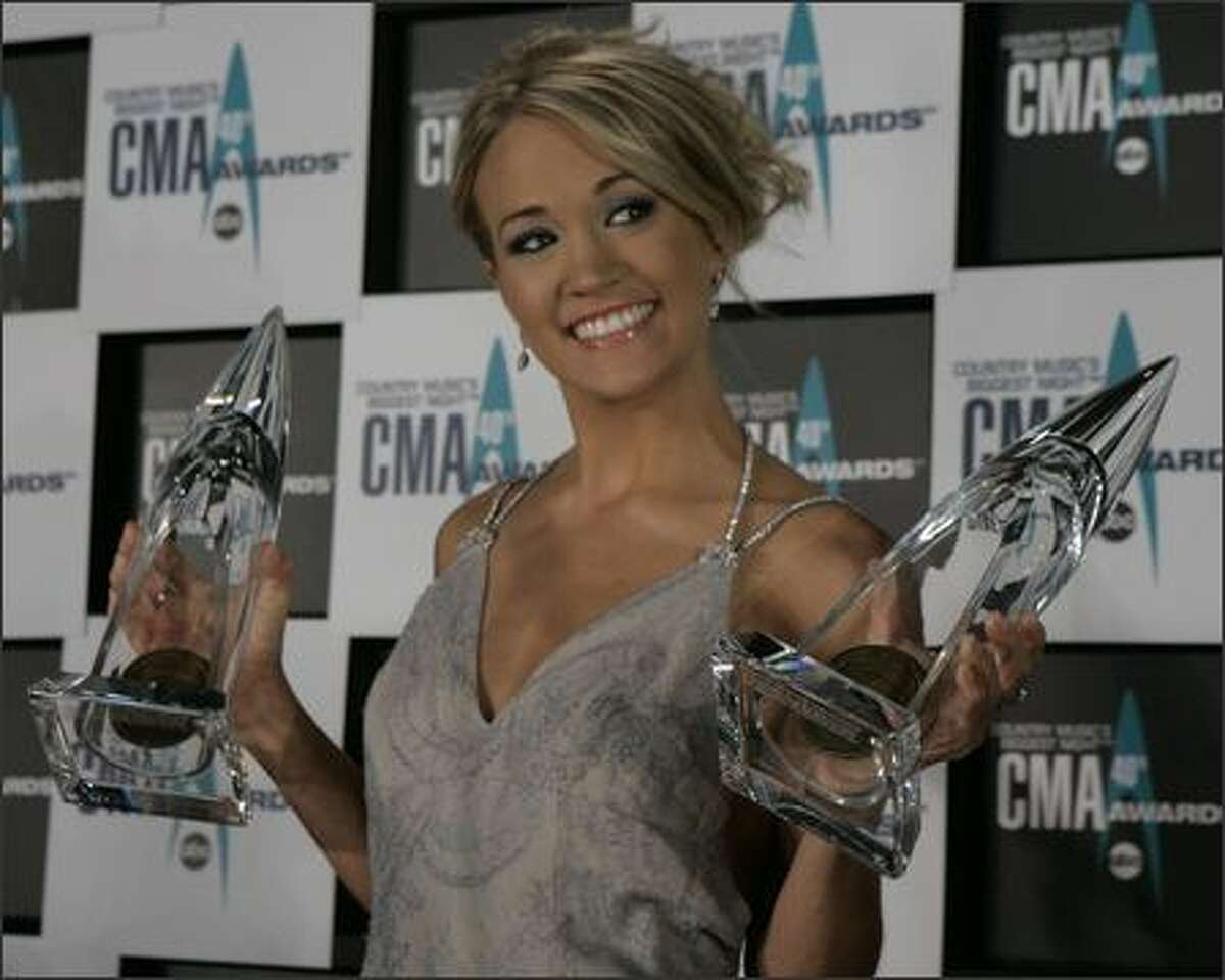 Carrie Underwood holds her Horizon and Female Vocalist of the Year Award trophies at the 40th Annual CMA Awards in Nashville, Tenn., on Monday. (AP Photo/Chitose Suzuki)