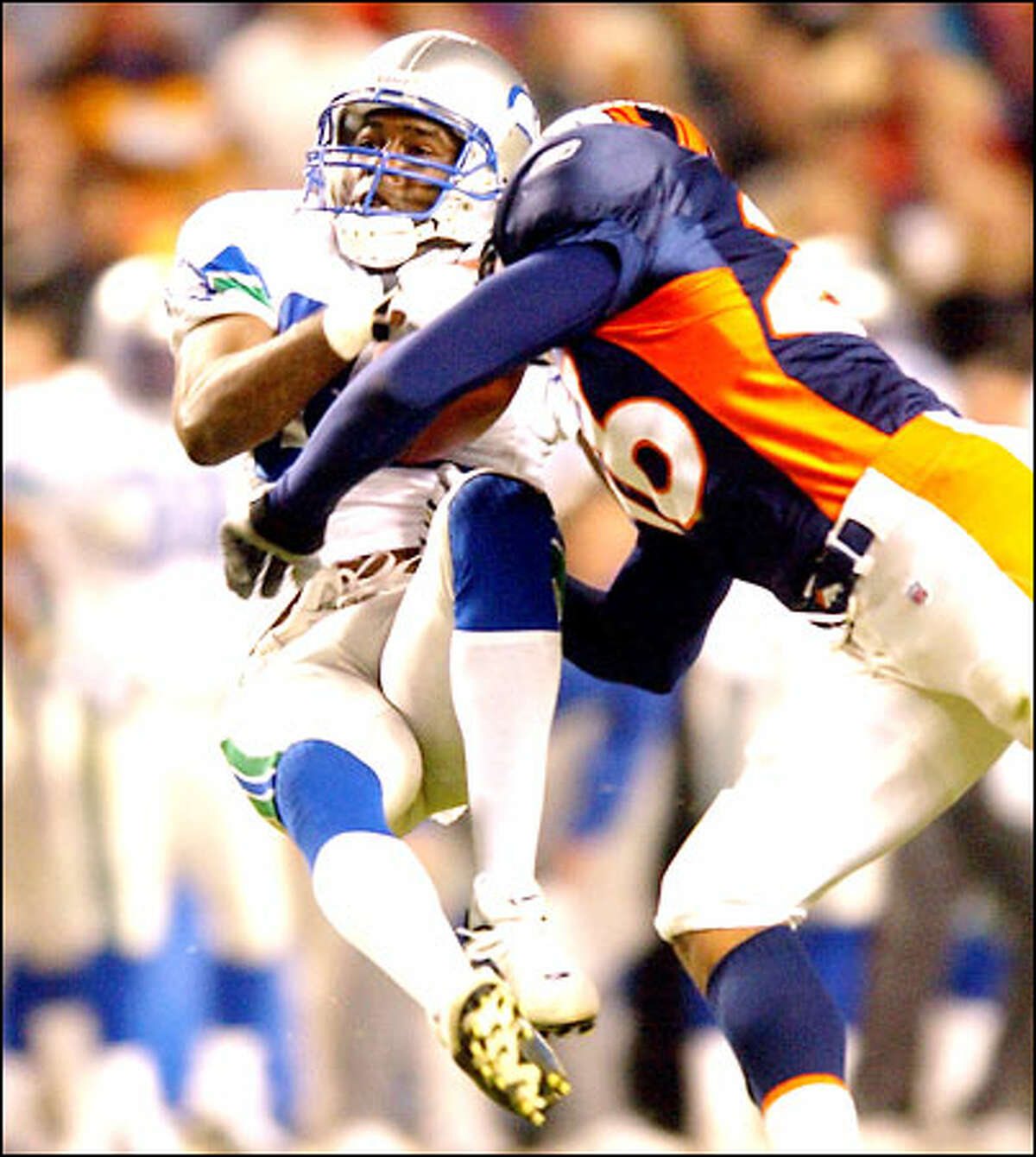 Wide receiver Darrell Jackson takes a hard hit from Broncos safety Eric Brown after making a 32-yard reception in the second quarter. Jackson scored the Seahawks' only touchdown.