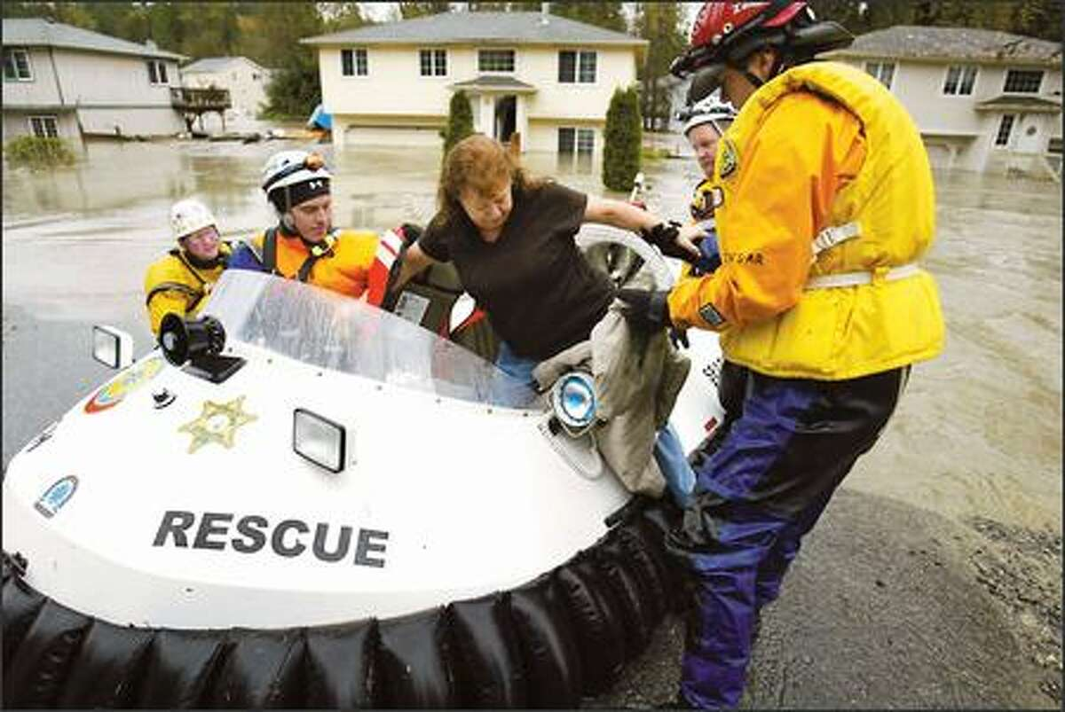 Snohomish County Search and Rescue bring Pauline Lindsey, center, to safety via Hovercraft on Jordan Rd in Granite Falls, WA, after she got trapped in her house by the rapidly rising waters of the Stillaguamish River.