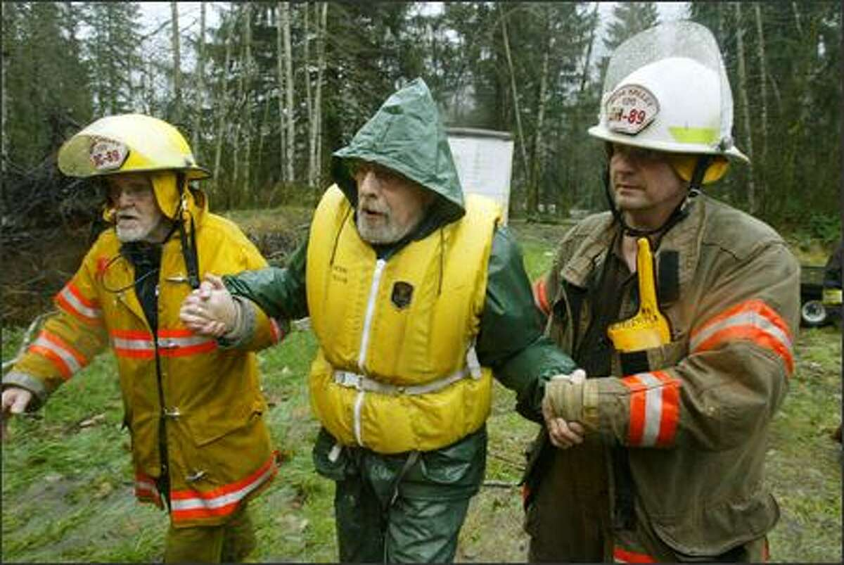 John Cornellison of Robe is escorted by firefighter Pete Iversen, left, and Chief Tim Bond of the Robe Valley Fire Department to an ambulance after being rescued from his home on the Stilliguamish River on Monday. Cornelleson was not injured and went to stay with a friend in Everett.