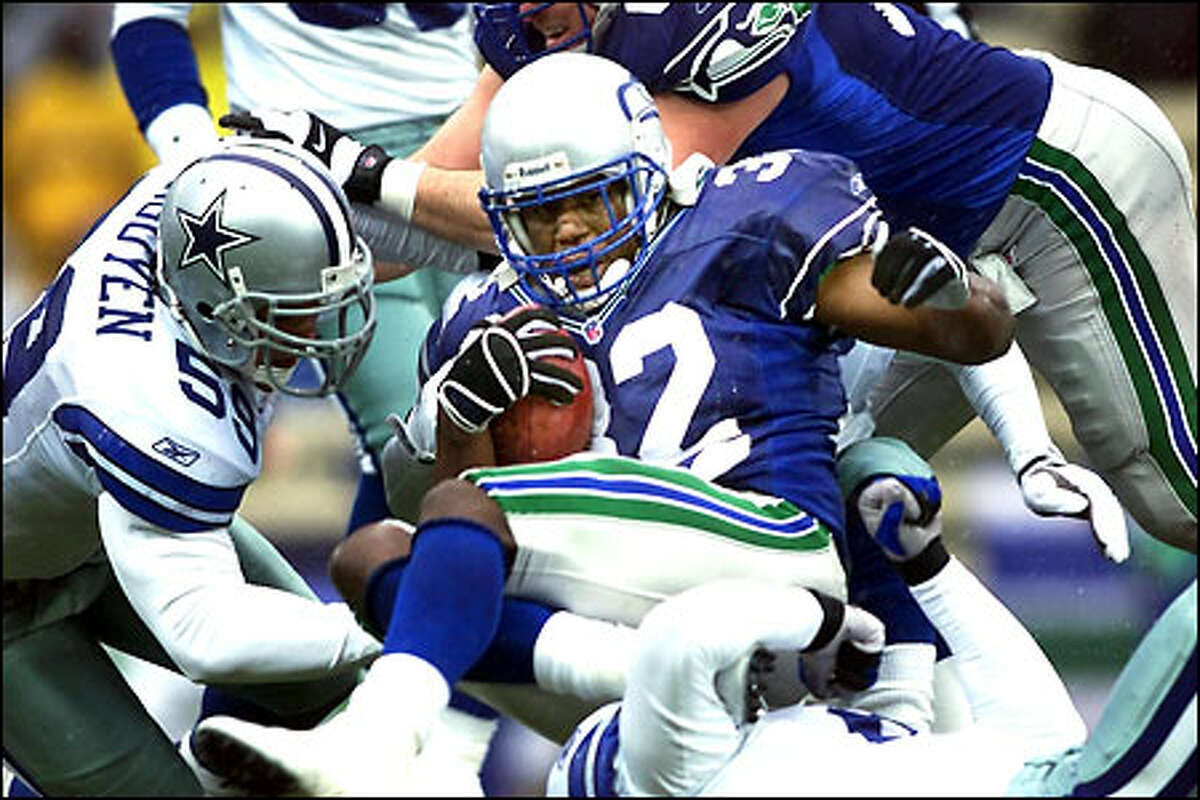 Ricky Watters pushes for extra yards against Cowboys linebacker Dat Nguyen (59). Watters rushed for 104 yards and a touchdown before spraining his right ankle in the fourth quarter.