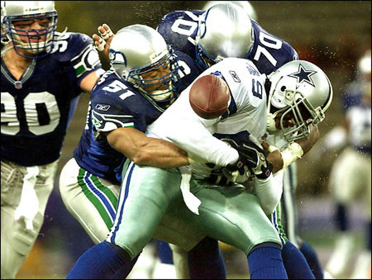 Linebacker Anthony Simmons (51) and end Michael Sinclair manhandle the Cowboys' Johnny Huggins.