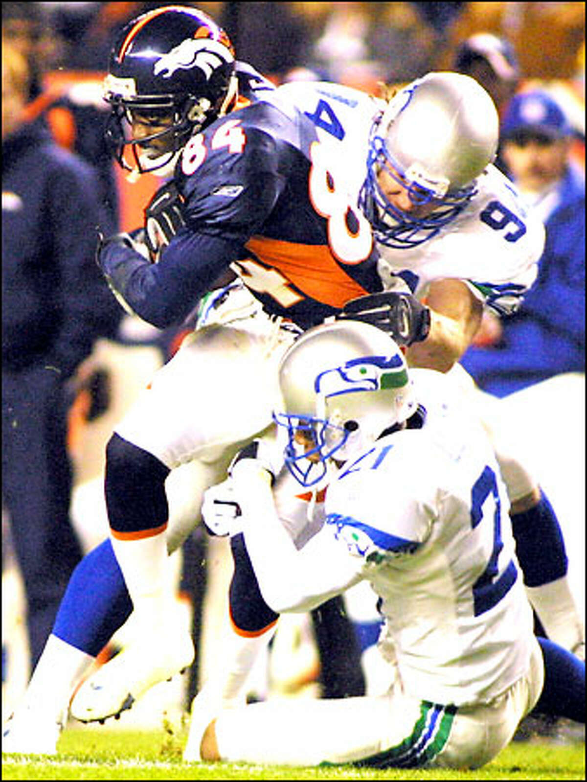 Denver's Chris Cole is tackled by Seahawks defenders Chad Brown, top, and Ken Lucas after a 12-yard reception.
