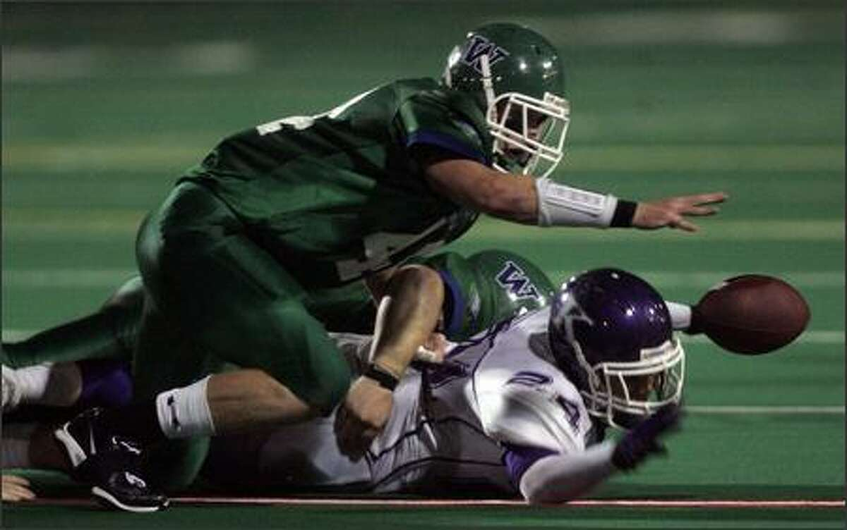Woodinville's Steve Low reaches for the ball after a fumble by Kamiak's Justin Glenn in the second quarter. Low recovered the fumble.