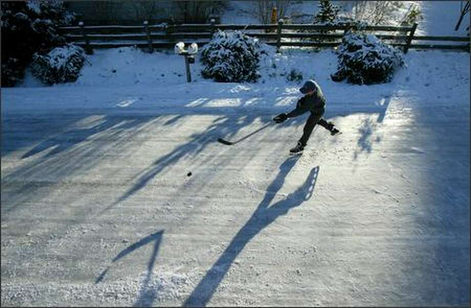 Garrett Duguay, 14, shoots his puck on normally busy North 150th Street at the intersection of Meridian Avenue North in Shoreline after a snowstorm and subsequent freeze shut many roads around the region. Photo: Joshua Trujillo, Seattlepi.com