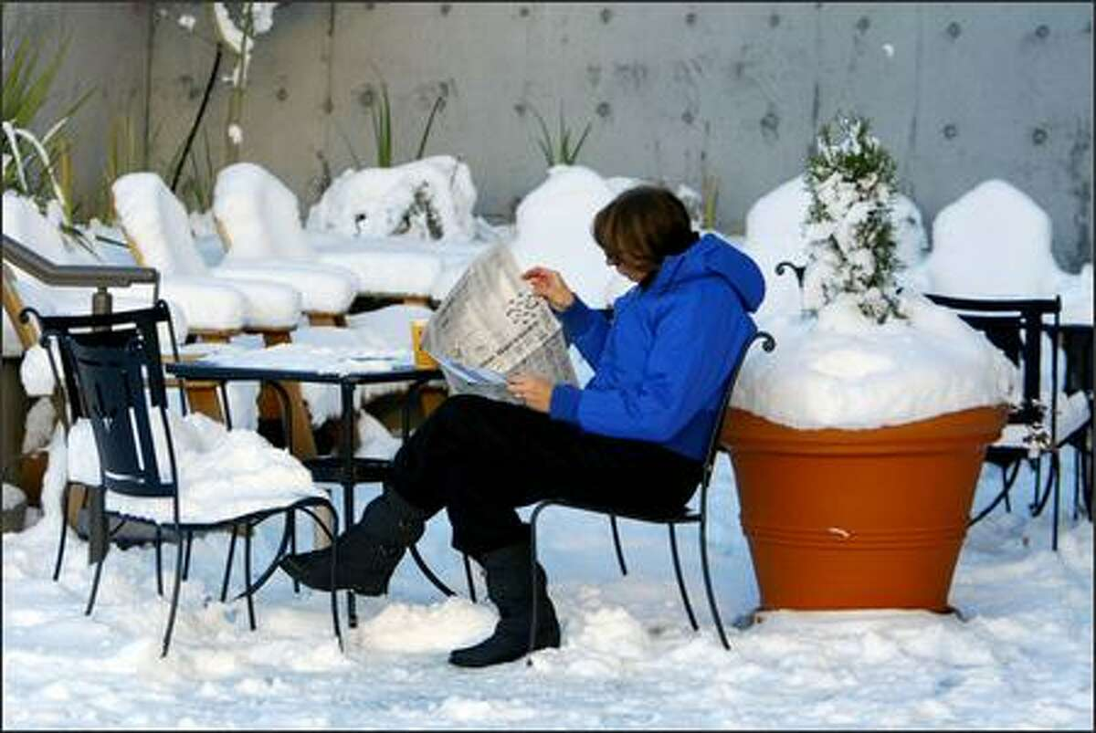Marcy Layman isn't bothered by the snow as she drinks a cup of tea outside a coffee shop in the Issaquah Highlands.