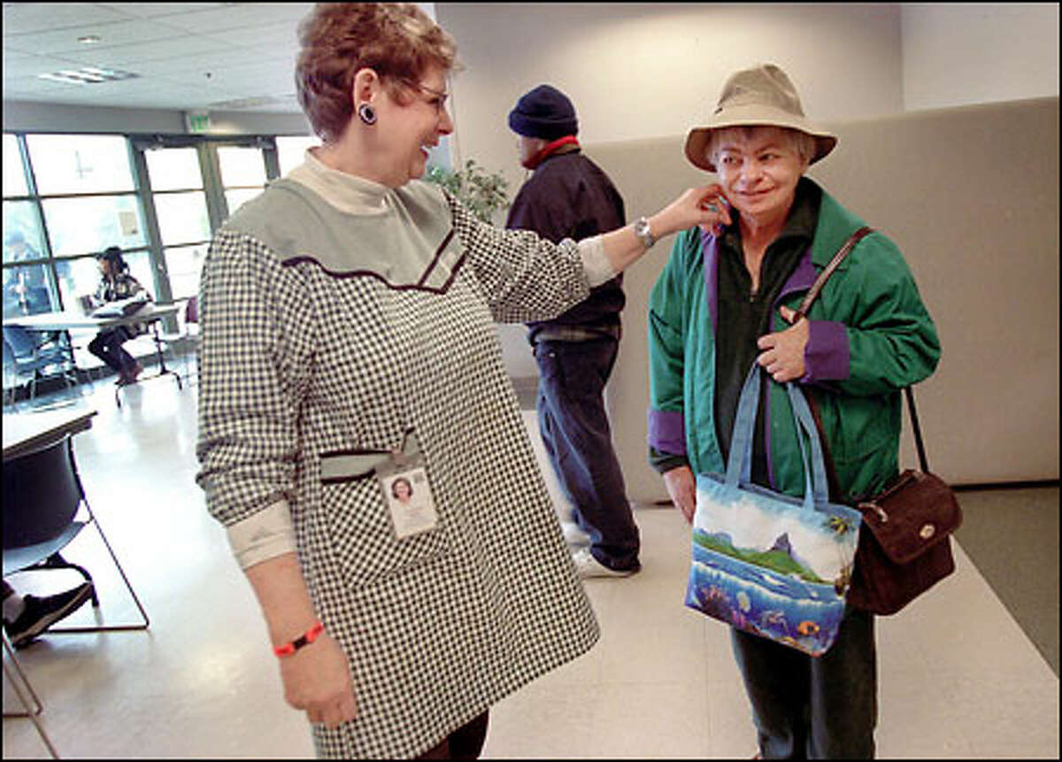 """Bird, left, strokes the cheek of her friend Judy Thompson during a break from her job at the Greater Lakes Mental Health Foundation in Lakewood. """"She is a good friend,"""" says Thompson of Bird. """"She cuts my hair and sometimes has me over to her apartment."""""""