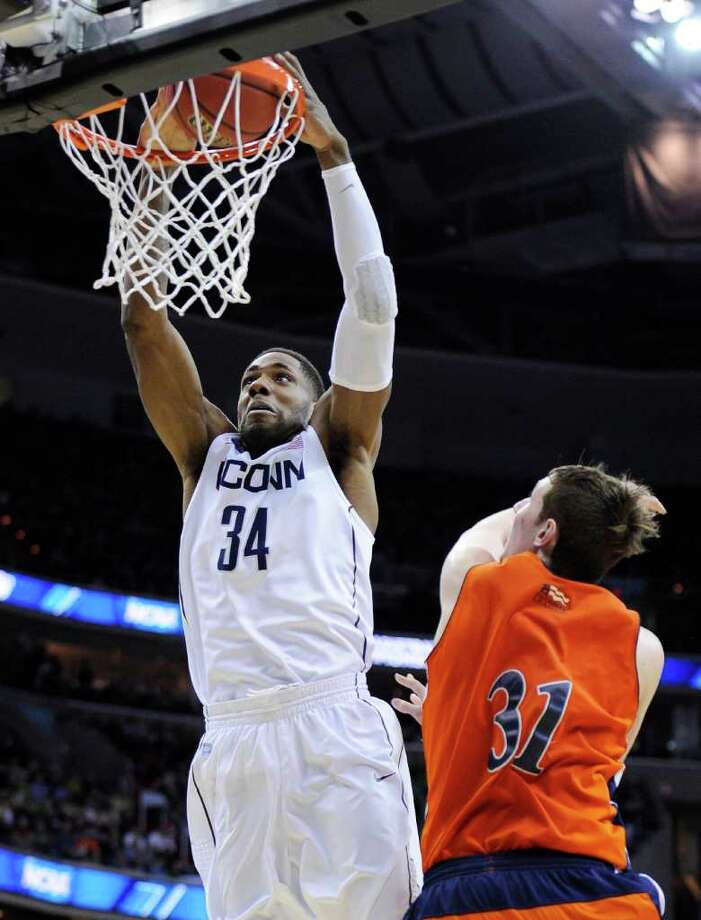 Connecticut forward/center Alex Oriakhi dunks over Bucknell center Mike Muscala during the second half of the West regional second round NCAA tournament college basketball game, Thursday, March 17, 2011, at the Verizon Center in Washington. Connecticut defeated Bucknell 81-52. (AP Photo/Nick Wass) Photo: AP