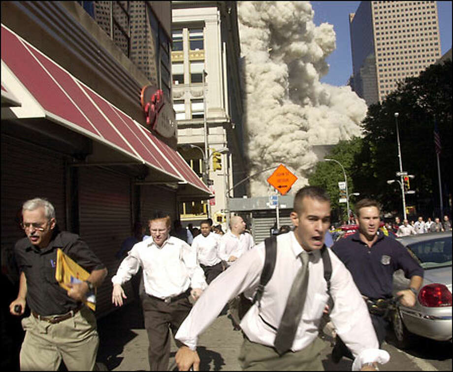 September 11: People run from the collapse of one of the twin towers of New York's World Trade Center. Photo: Suzanne Plunkett, The Associated Press