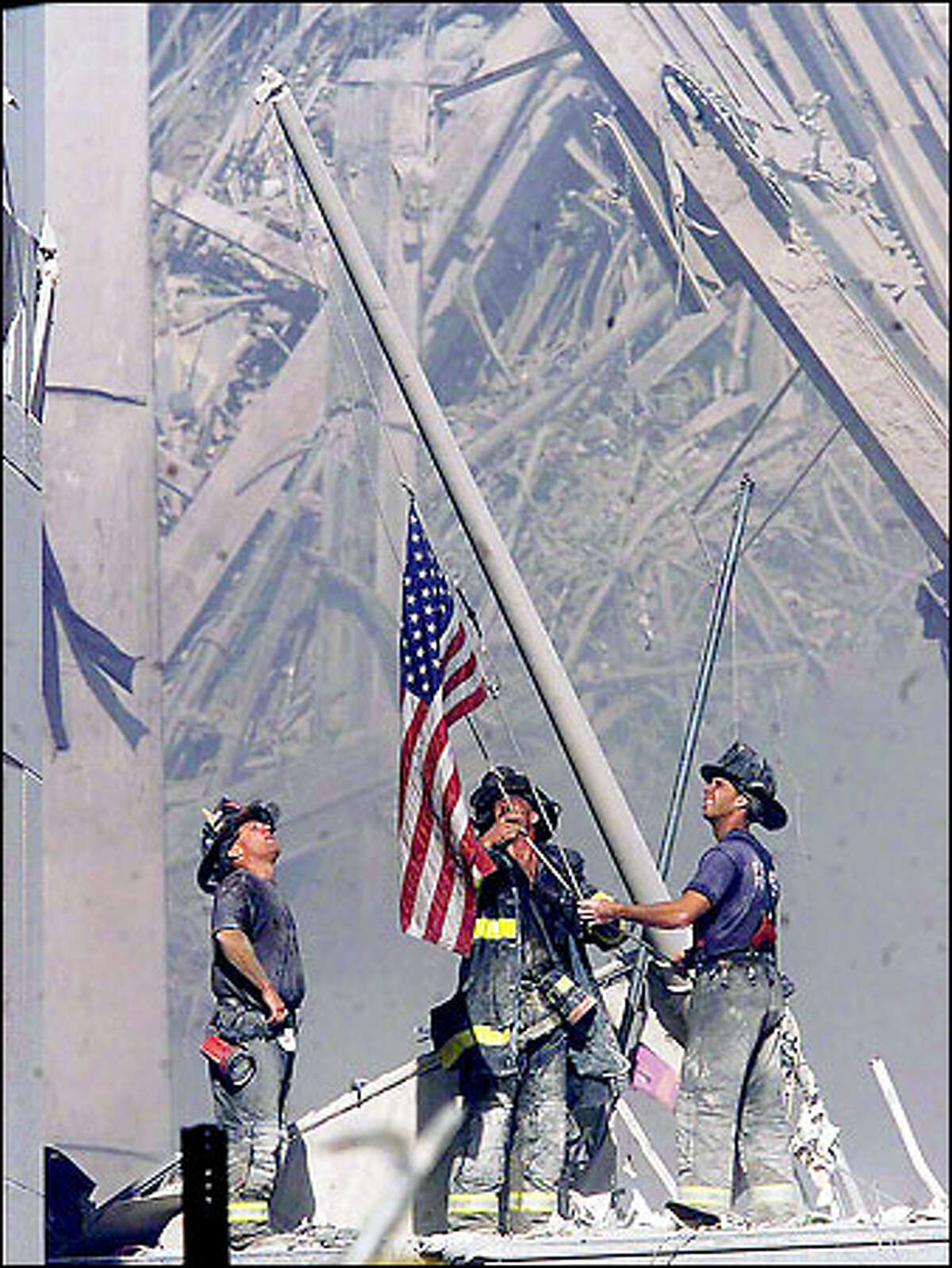 September 11: Brooklyn firefighters George Johnson, left, of Ladder 157, Dan McWilliams, center, of Ladder 157, and Billy Eisengrein, of Rescue 2, raise a flag at the World Trade Center in New York.