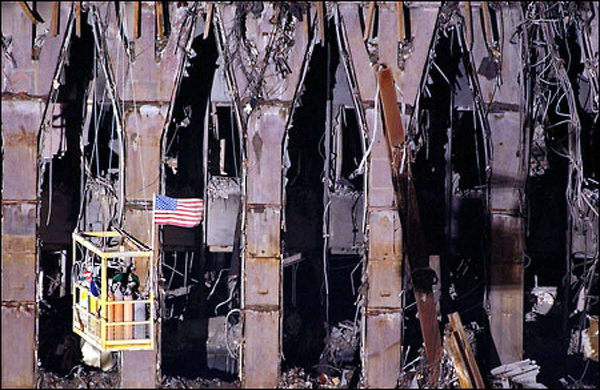 September 11: Workers are suspended from a crane in front of the remains of the North Tower.