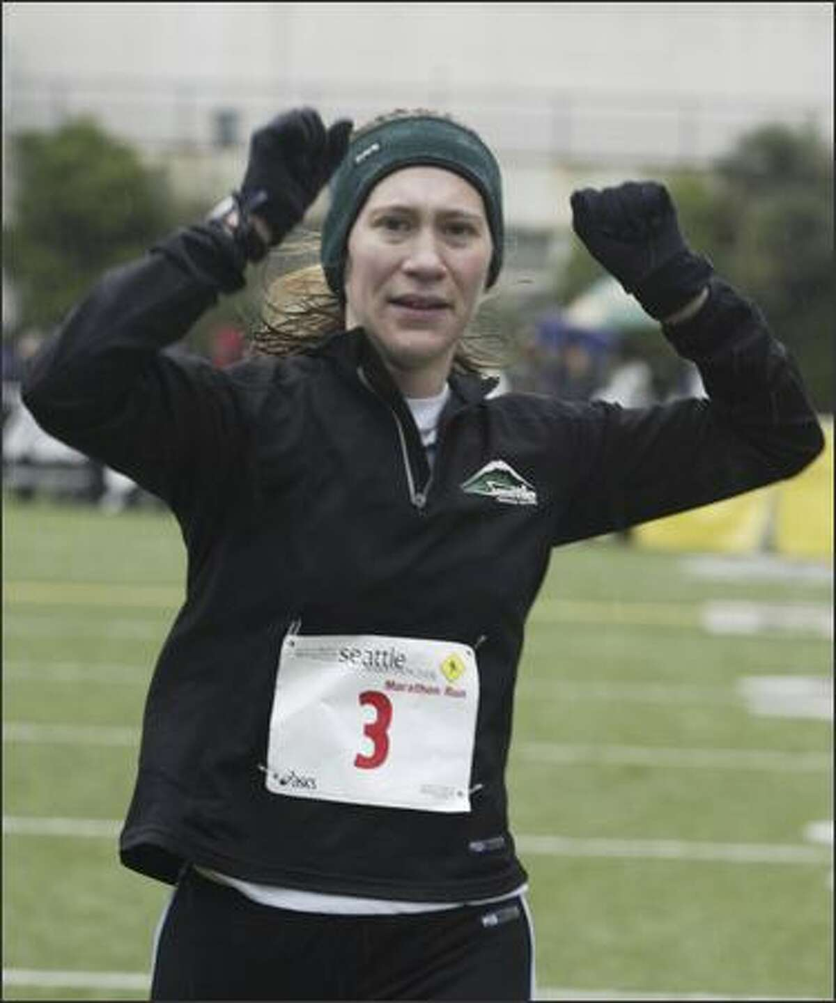 Trisha Steidl, of Seattle, crosses the Seattle Marathon finish line to place first in the Women's Marathon with a time of 3:01:36.
