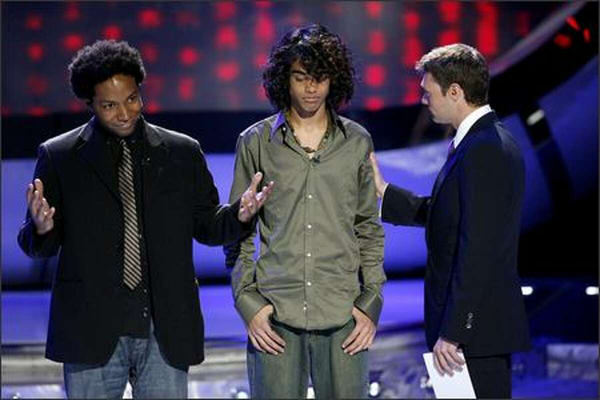Brandon Rogers (left) is eliminated from competition on March 14 as Sanjaya Malakar (center) hears the good news -- it's not him. Ryan Seacrest is at right.