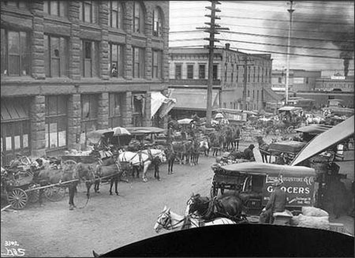 Before the opening of Seattle's Pike Place Market in 1907, farmers sold their fruit and vegetables to the customer through brokers or other middlemen. Much of this wholesale produce trade took place in the so-called Commission District, in the area of Railroad and Western Avenues and Columbia and Marion Streets. Once the wholesalers took their commissions, customers paid more and farmers received only a percentage of the price. Shown are wagons on Marion Street in 1905.