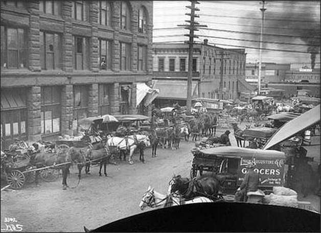 Before the opening of Seattle's Pike Place Market in 1907, farmers sold their fruit and vegetables to the customer through brokers or other middlemen. Much of this wholesale produce trade took place in the so-called Commission District, in the area of Railroad and Western Avenues and Columbia and Marion Streets. Once the wholesalers took their commissions, customers paid more and farmers received only a percentage of the price. Shown are wagons on Marion Street in 1905. (seattlepi.com) Photo: Museum Of History And Industry