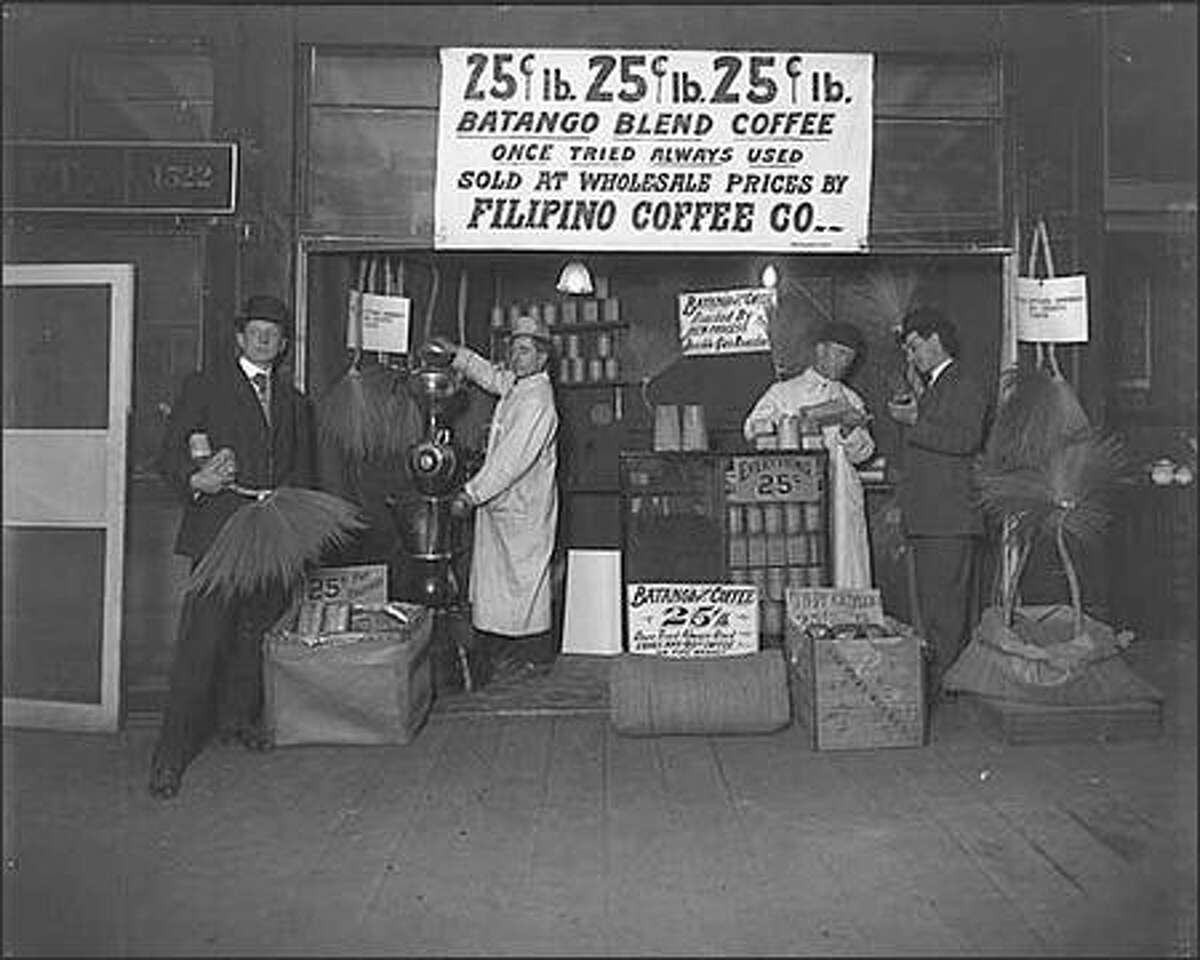 The address number 1522 on the wall behind this coffee display indicates the photo was taken in the Pike Place Market ca. 1909.