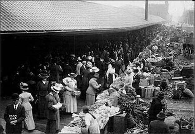 "Seattle's Pike Place Market began as a jumble of farm carts, produce, and shoppers on Western Avenue. Starting in 1911, farmers could set up stalls in the city's new covered arcade. The ""dry row"" of stalls was inside the arcade, and the ""wet"" stalls were outside. All stalls rented for 20 cents a day. (seattlepi.com) Photo: Museum Of History And Industry"