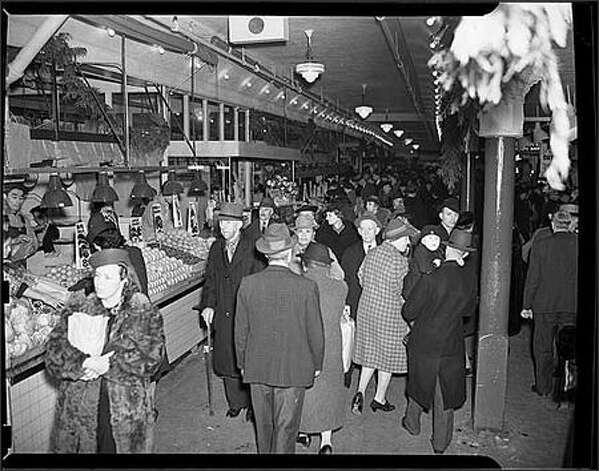 Ever since Seattle's Pike Place Market opened for business in 1907, it has provided a place for the region's farmers to sell fruits, vegetables, and other foodstuffs directly to city dwellers. In this 1940 photo, crowds walk through stalls displaying fresh produce. (seattlepi.com file) Photo: Museum Of History And Industry