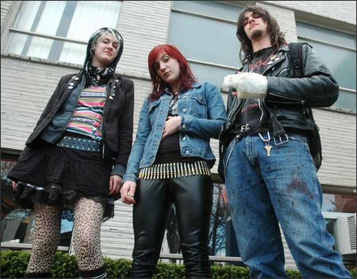 (From left) Aubrie, Angela and Jonny stop for a photo as they walk down Broadway on Saturday, March 31.