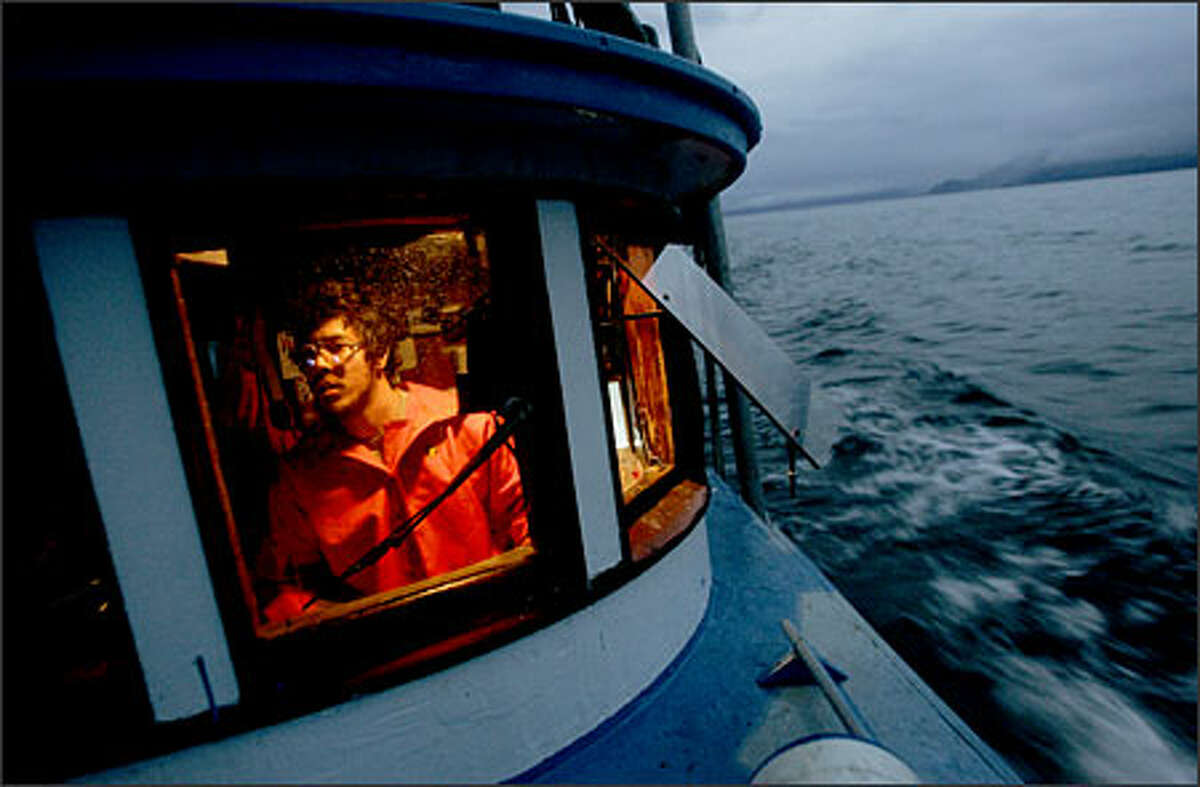 Jonah Knutson pilots the Loki, a fishing boat, at about 4 a.m. halfway through a two-day opening in Clarence Strait.Kane: This is one of my favorite shots from my favorite project this year. It's from a story about Pete Knutson and his son Jonah, Seattle gill netters who fish in Alaska during the summer. After sleeping maybe an hour or two on a tiny section of floor that was wet with fish slim, I arose at about 4 a.m. and staggered out onto the bow to wait for this shot. The sun was just hinting at rising and as any photographer knows, that's some good light.