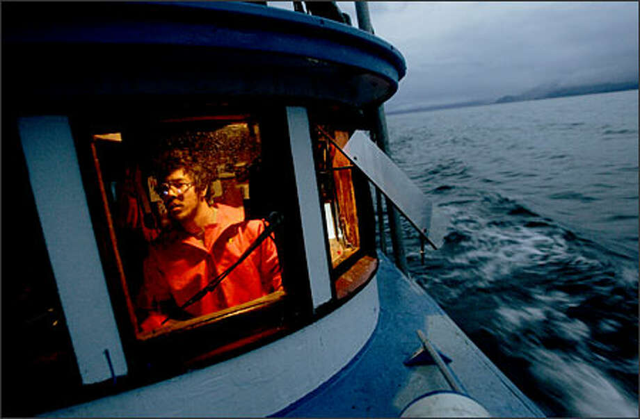 Jonah Knutson pilots the Loki, a fishing boat, at about 4 a.m. halfway through a two-day opening in Clarence Strait.Kane:This is one of my favorite shots from my favorite project this year. It's from a story about Pete Knutson and his son Jonah, Seattle gill netters who fish in Alaska during the summer. After sleeping maybe an hour or two on a tiny section of floor that was wet with fish slim, I arose at about 4 a.m. and staggered out onto the bow to wait for this shot. The sun was just hinting at rising and as any photographer knows, that's some good light. Photo: Mike Kane, Seattle Post-Intelligencer